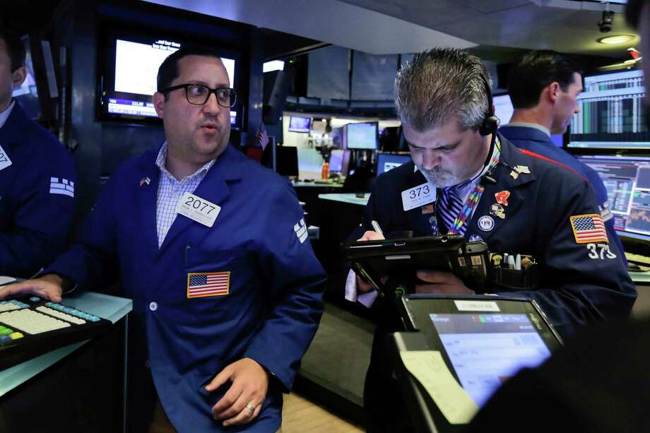 Specialist Brian Fairbrother, left, works with traders at the post that handles Kroger on the floor of the New York Stock Exchange, Friday, June 16, 2017. Major U.S. indexes are slightly lower in early trading on Wall Street, but grocery stores and other retailers are plunging after Amazon said it would buy Whole Foods Market. (AP Photo/Richard Drew) Photo: Richard Drew, STF / AP