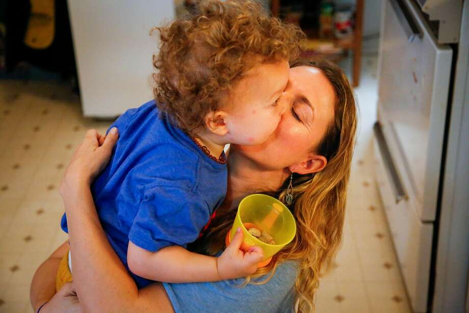 Julie Panebianco kisses her son, Niko Gregory, 1, goodbye for the day before her husband, Jon Gregory, takes him to day care in San Francisco. Photo: Nicole Boliaux, The Chronicle