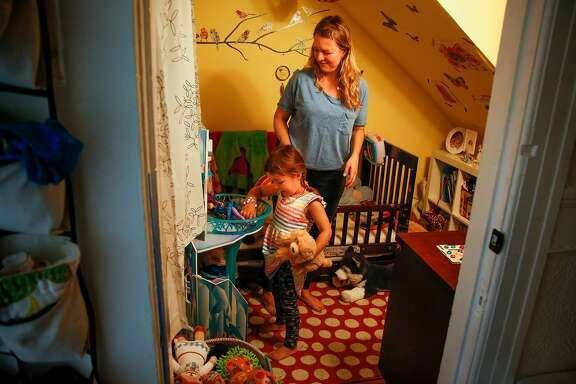 Julie Panebianco plays with her her daughter Daisy Gregory, 4, in her small room in San Francisco on Friday, June 16, 2017. Panebianco cut down her teaching schedule from five classes to three so she could save money on childcare.