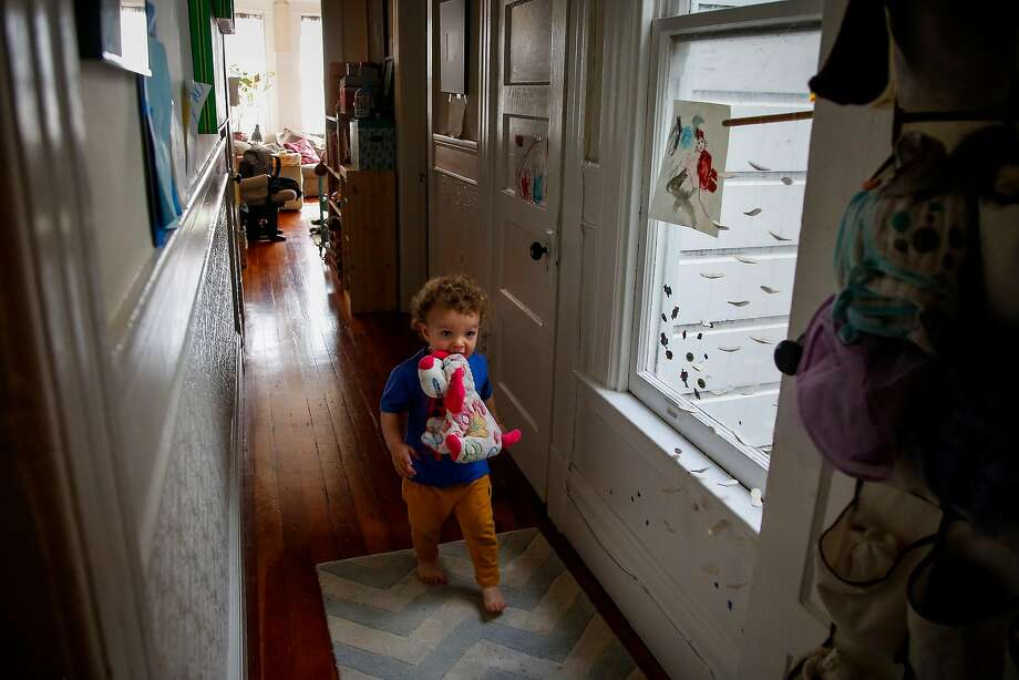 Niko Gregory, 1, carries sister Daisy's stuffed animal in his mouth through his family's one-bedroom apartment in San Francisco. Photo: Nicole Boliaux, The Chronicle