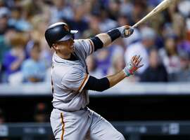 San Francisco Giants' Buster Posey follows through on a two-run home run off Colorado Rockies relief pitcher Scott Oberg during the seventh inning of a baseball game Thursday, June 15, 2017, in Denver. The Rockies won 10-9. (AP Photo/David Zalubowski)
