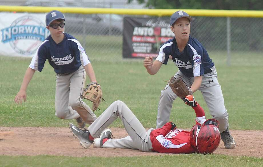 Norwalk Linen shortstop Will Singewald, right, makes an outside after tagging out Bonaddio Construction's Henry Stefanowicz on a stolen-base attempt during Friday's Norwalk Little League Majors Division championship game at Broad River Field in Norwalk. Norwalk Linen's Anthony Lamotte backs up the play. Photo: John Nash / Hearst Connecticut Media / Norwalk Hour