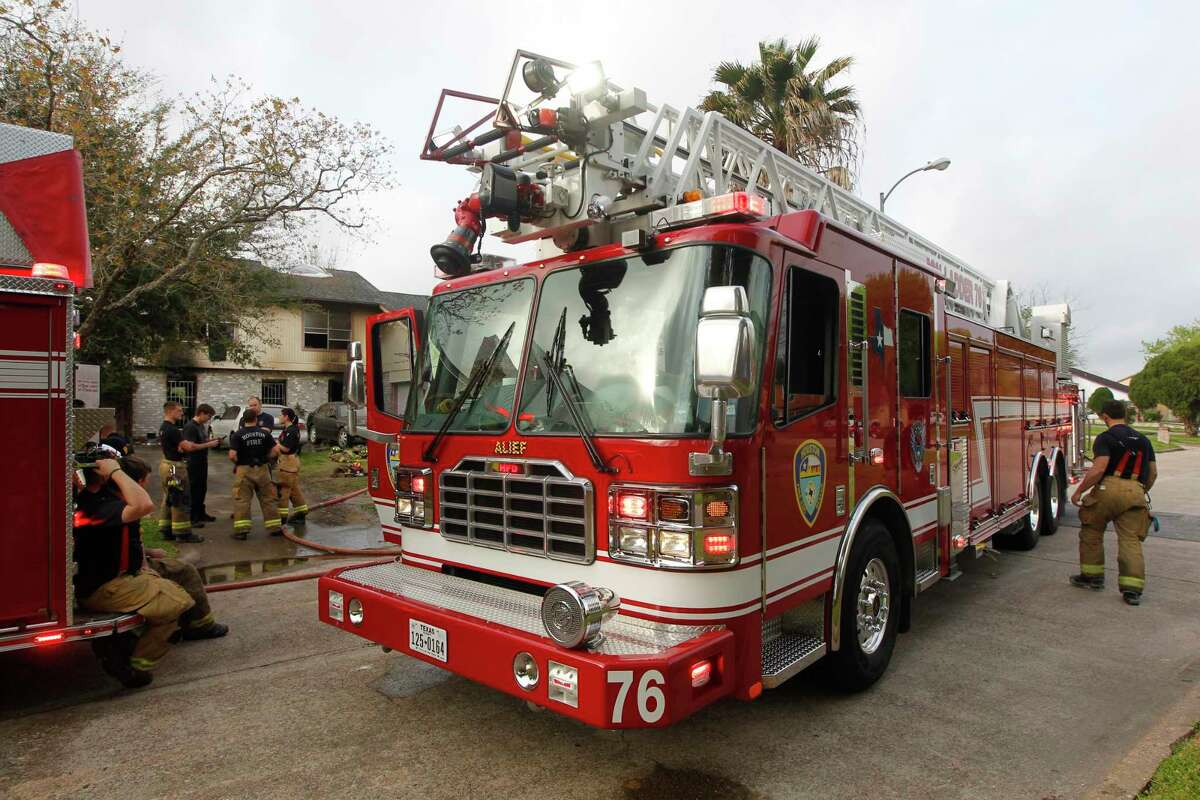 Houston Fire Department members investigate a house fire. (J. Patric Schneider / For the Chronicle )