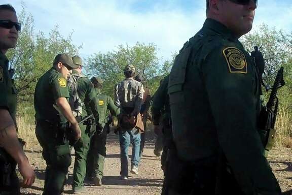 This Thursday June 15, 2017, photo provided by No More Deaths/No Mé¡s Muertes, an organization that provides care for migrants along the Mexican border, shows Border Patrol agents detaining an unidentified person in the Arizona desert. Border Patrol agents descended on the medical camp set up in the Arizona desert near the border to provide refuge and water for migrants in the scorching summer heat, arresting four men who were receiving aid after spending several days in the desert. (No More Deaths/No Mé¡s Muertes via AP)