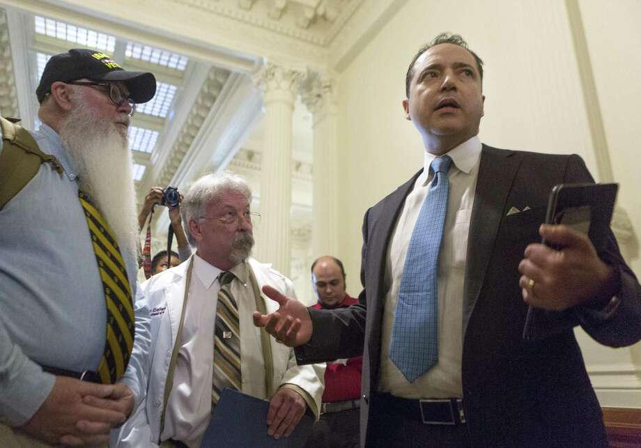 Sen. Jose Menendez, from right, speaks with Lang Coleman and Ret. Major David Bass at the Texas Capitol in Austin. Coleman, a former military psychologist who is an advocate for medical marijuana treatment of post tramautic stress disorder, is challenging the way the state issued its first conditional licenses for medical marijuana. Photo: Stephen Spillman /Stephen Spillman / stephenspillman@me.com Stephen Spillman