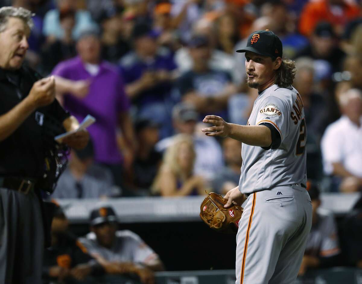 San Francisco Giants starting pitcher Jeff Samardzija, right, directs a remark toward home plate umpire Gary Cederstrom as Samardzija is pulled from the mound after walking Colorado Rockies' DJ LeMahieu to lead off the bottom of the seventh inning of a baseball game Friday, June 16, 2017, in Denver. The Rockies won 10-8. (AP Photo/David Zalubowski)