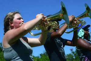 Members of the Norwalk High School Marching Bears, including french horn player Sam Perrottelli, practice during the high school's annual summer band camp at Andrews Field in Norwalk. The Board of Education is expected to vote Tuesday on $1.99 million in budget cuts that would eliminate a large swath of services and programs for the city's youth.