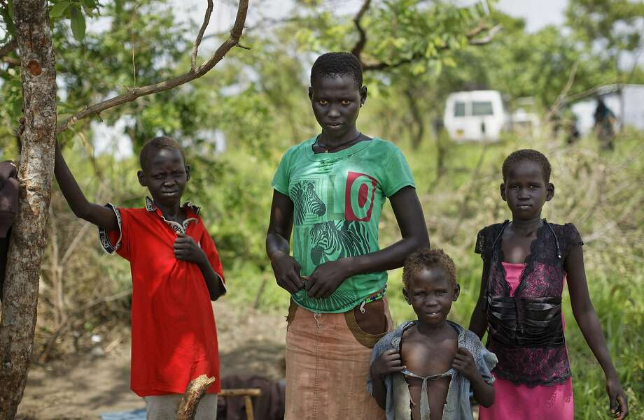 In this photo taken Tuesday, June 6, 2017, Bakita Juma, 15, center, both of whose parents were killed, stands with her sister Juan, 8, right, a friend, center-right, and brother Luka, 12, left, near to her foster mother's hut, in the Bidi Bidi refugee settlement in northern Uganda. One of the consequences of South Sudan's civil war has been the thousands of unaccompanied or separated children fleeing without parents or guardians, of which it is estimated around 9,000 have crossed into Uganda since July. (AP Photo/Ben Curtis) Photo: Ben Curtis, Associated Press