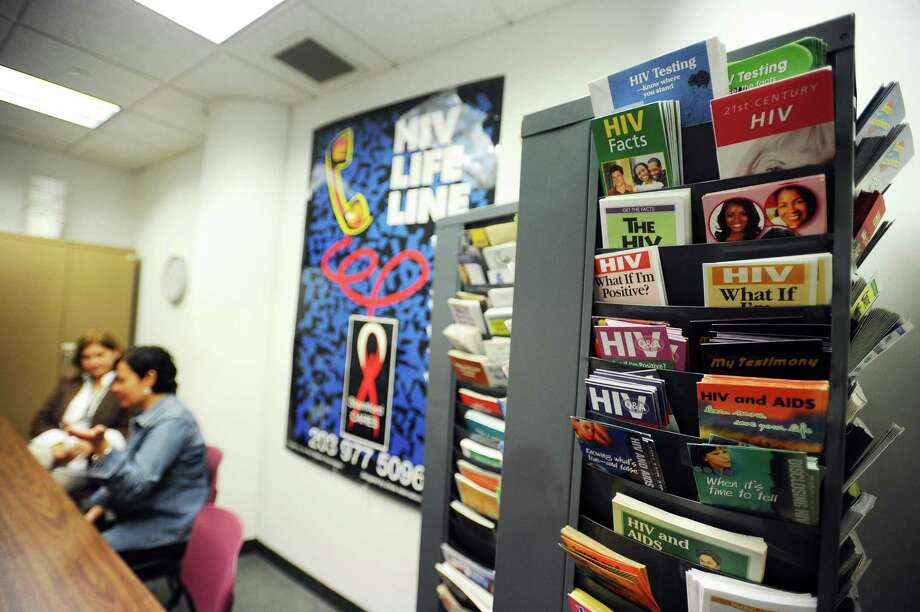 Dozens of HIV and other sexual health pamphlets sit in the corner while employees Deborah Arrieta and Ivette Gonzalez discuss next year's city budget, which cut the city-run HIV prevention and testing program, inside Government Center. Photo: Michael Cummo / Hearst Connecticut Media / Stamford Advocate