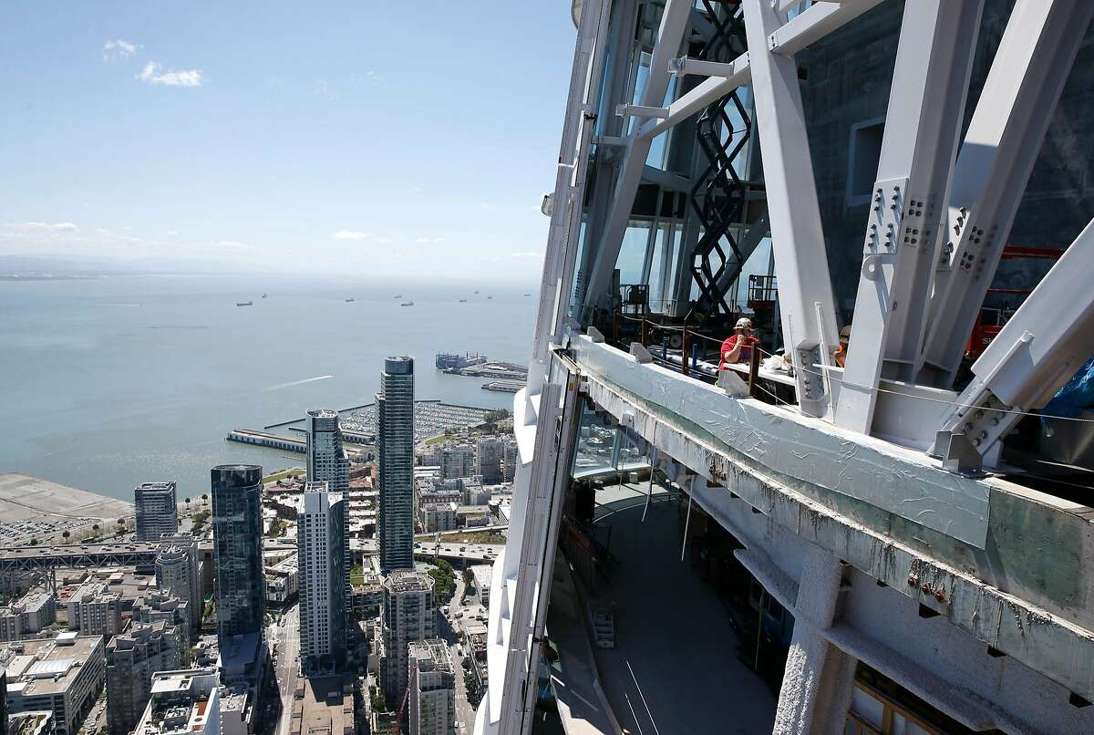 A construction crew works near the top of the 1,070-foot Salesforce Tower before a large panel of LED lights is installed around the crown for artist Jim Campbell's light installation in San Francisco, Calif. on Friday, May 12, 2017.
