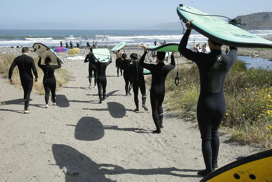Surfers make their way into Pacifica State Beach. Photo: Santiago Mejia, The Chronicle