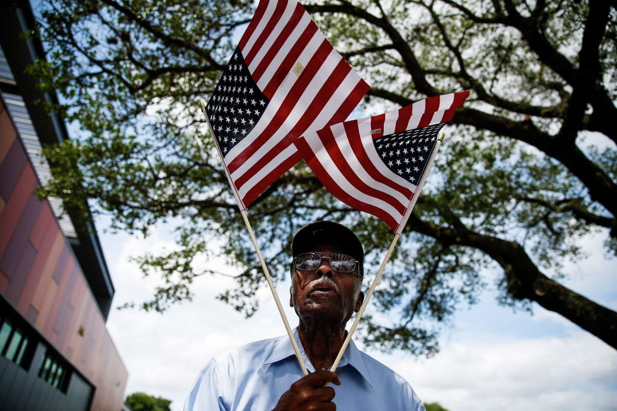 """John Tayor, a resident of the Third Ward since 1957, holds american flags in a """"V for victory"""" as he walks around Emancipation Park during the rededication ceremony for the space after it underwent a $33 million renovation Saturday, June 17, 2017 in Houston."""