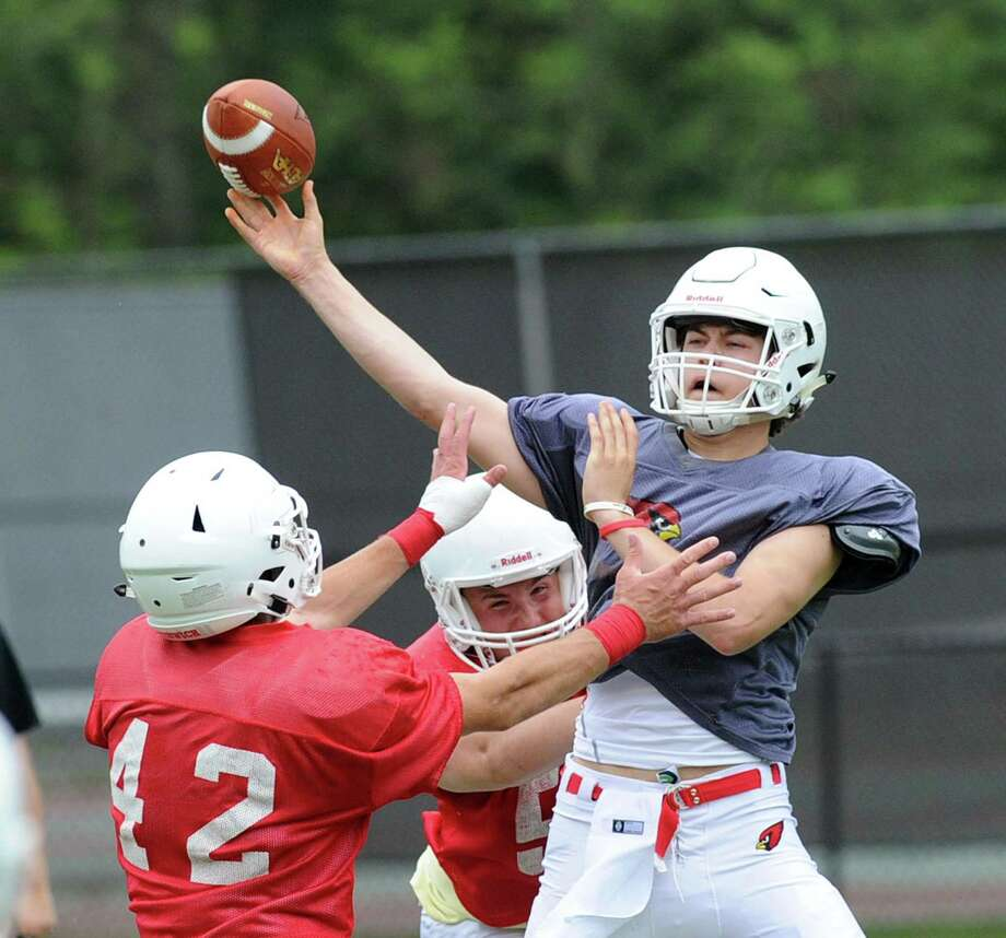 White quarterback Gavin Muir, right, just gets off a pass as he is pressured by two red players including Gramoz Bici (42) during the annual Greenwich High School Red vs. White spring scrimmage at Cardinal Stadium, Greenwich, Conn., Saturday, June 17, 2017. Photo: Bob Luckey Jr. / Hearst Connecticut Media / Greenwich Time