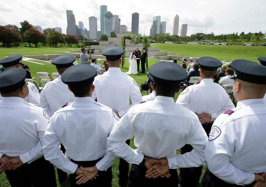 Houston Police Cadets watch the wedding of Cynthia Martin and Daniel Florek officated by HPD chaplain Monty Montgomery at the Houston Police Officer Memorial Saturday, June 17, 2017, in Houston. Cynthia Martin is the daughter of Richard Martin, a Houston Police Officer who died in the line of duty on May 18, 2015. ( Melissa Phillip / Houston Chronicle ) Photo: Melissa Phillip, Staff / © 2017 Houston Chronicle