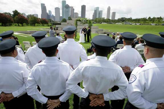 Houston Police Cadets watch the wedding of Cynthia Martin and Daniel Florek officated by HPD chaplain Monty Montgomery at the Houston Police Officer Memorial Saturday, June 17, 2017, in Houston. Cynthia Martin is the daughter of Richard Martin, a Houston Police Officer who died in the line of duty on May 18, 2015. ( Melissa Phillip / Houston Chronicle )