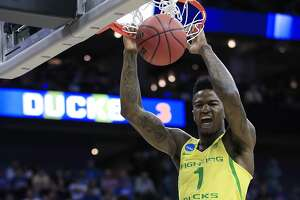FILE - In this Thursday, March 23, 2017, file photo, Oregon forward Jordan Bell (1) dunks over Michigan guard Zak Irvin (21) during the first half of a regional semifinal of the NCAA men's college basketball tournament in Kansas City, Mo. The junior is averaging 10.9 points and 8.6 rebounds as a potential X-factor for the Ducks entering Saturday's game against North Carolina. (AP Photo/Orlin Wagner, File)