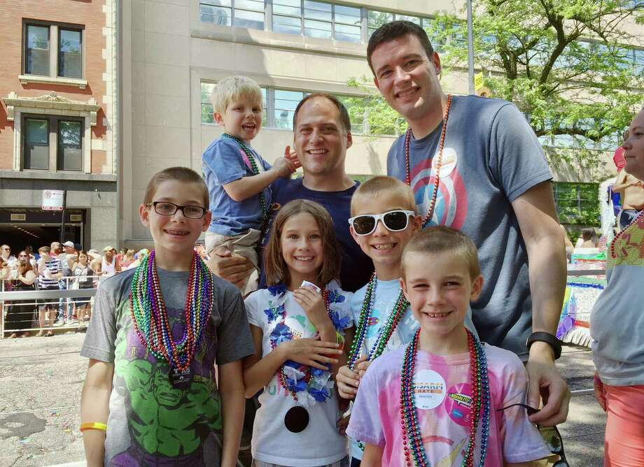This June 26, 2016 photo provided by the family shows Kevin Neubert, background center, and Jim Gorey with their adopted children, from left, Luke, Derek, Natalie, Zach, and Jacob at the Chicago Pride Parade. Following night classes to qualify as foster parents, Neubert and Gorey agreed in December 2011 to provide a temporary home for a newborn baby. A stay intended to last only for a few days was extended into several months, and Neubert and Gorey learned that the baby had four older siblings who were also in foster care. They eventually decided to adopt all five. (Nicole Gifford Baugh/Jim Gorey via AP) Photo: Nicole Gifford Baugh, HONS / Jim Gorey