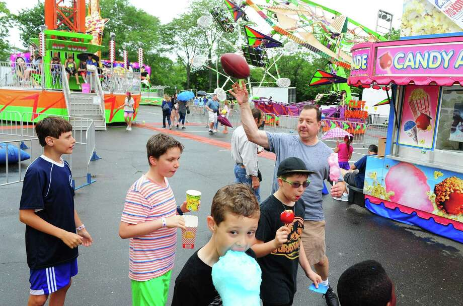 John Caracato, of Westport, tosses a football that got loose at the tire toss to his son's friend Justin Juliano, 11, left, during the Westport Woman's Club's Yankee Doodle Fair in Westport, Conn., on Saturday June 17, 2017. John's son Colin is standing next to Justin. The annual family fair continues on Sunday, 1 PM to 5 PM. Photo: Christian Abraham / Hearst Connecticut Media / Connecticut Post