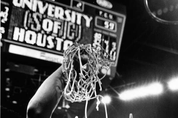 03/13/1983 - A jubilant Larry Micheaux - surrounded by equally happy teammates - shows off a souvenir net cut down after the Houston Cougars defeated TCU, 62-59, Saturday in Reunion Arena in Dallas to win the Southwest Conference title.