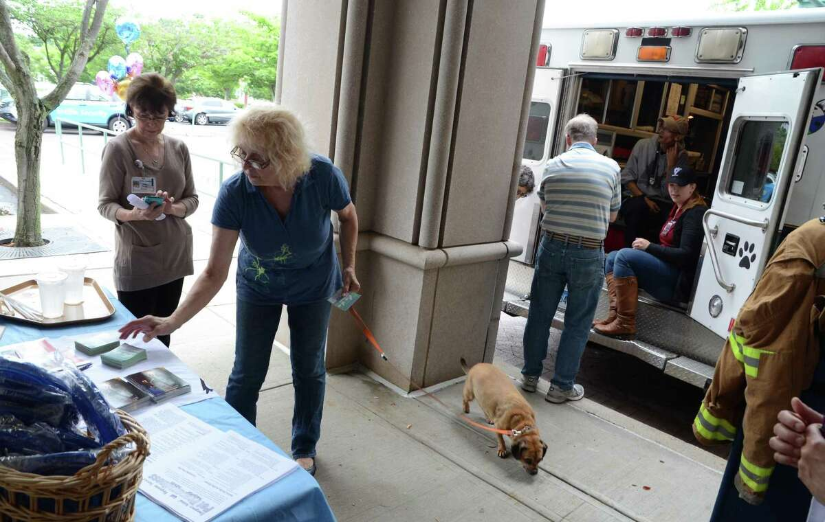 Visiting with her dog Melinda, Carol Zolovchik, of Ansonia, grabs some pamphlets during a meet-and-greet with the Connecticut Emergency Animal Response Service (EARS) at the hospital in Derby, Conn., on Saturday June 17, 2017. EARS is a team of volunteer first responders trained for rapid-response to