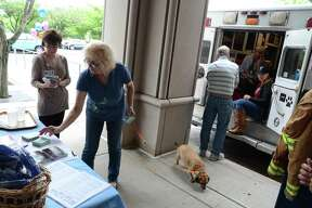 "Visiting with her dog Melinda, Carol Zolovchik, of Ansonia, grabs some pamphlets during a meet-and-greet with the Connecticut Emergency Animal Response Service (EARS) at the hospital in Derby, Conn., on Saturday June 17, 2017. EARS is a team of volunteer first responders trained for rapid-response to ""all-hazard"" animal emergencies within Connecticut. For more information about EARS, visit www.earsct.org. The event was hosted by People and Animals Working in Spirit (P.A.W.S.), Griffin Hospital's Pet Therapy Program. P.A.W.S. founder Ruth Tuccio, stands at left during the event."