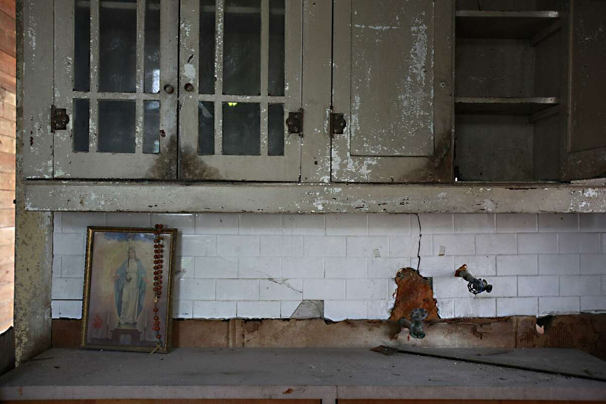 A framed image of Mother Mary with a rosary is set in Miguel S. Calzada's house kitchen, surrounded by broken cabinets and wore out tiles.