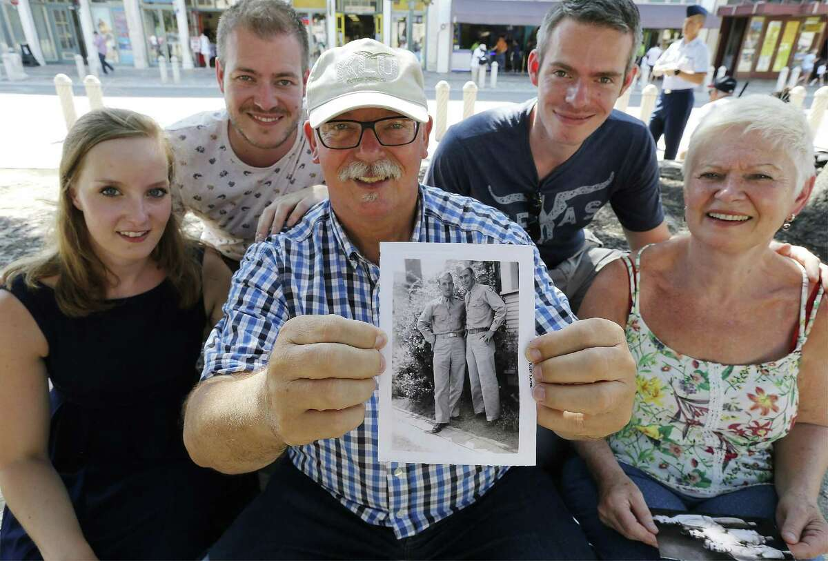 Don Schmitz (center) of Margraten, Netherlands and his family: wife Monique (front right), his two sons Philippe (top left) and Raymond (top right) and Phillipe's girlfriend Viony Uroemen (left) pay a visit to San Antonio on Friday, June 16, 2017. Schmitz holds a photo that contains the image of a World War II American soldier killed in the Netherlands and, for the past 20 years, has been the caretaker of the soldier's grave. The soldier, Norman Harold Smith (left in picture) shown with his younger brother, Thomas Anthony Smith, was from San Antonio and, with the help of the Internet and some friendly Texans, he connected with family members in San Antonio this week. Schmitz lives in the Dutch village where the World War II Netherlands American Cemetery and Memorial entomb 8,301 soldiers who perished during WWII. When Schmitz signed up to care for a headstone that only had the name of Norman Harold Smith, the Dutchman began his journey to find relatives with the deceased soldier from San Antonio. (Kin Man Hui/San Antonio Express-News)