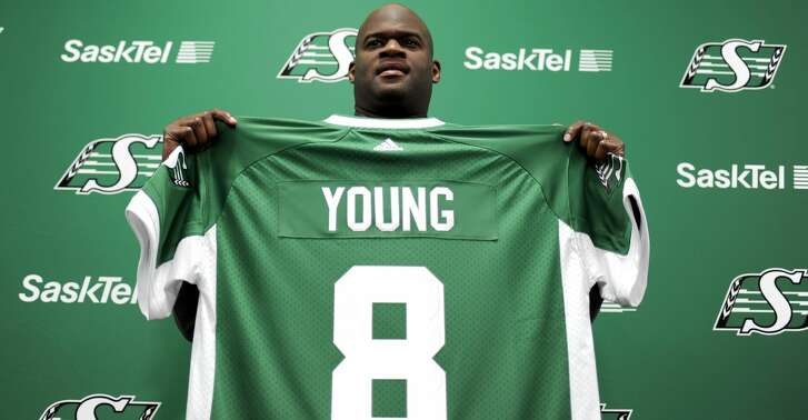Vince Young, a former quarterback with the NFL's Philadelphia Eagles and Tennessee Titans, holds up a jersey during a news conference at Mosaic Stadium, Thursday, March 9, 2017, in Regina, Saskatchewan, after signing with the CFL's Saskatchewan Roughriders in Regina Thursday, March 9, 2017. (Mark Taylor/The Canadian Press via AP)