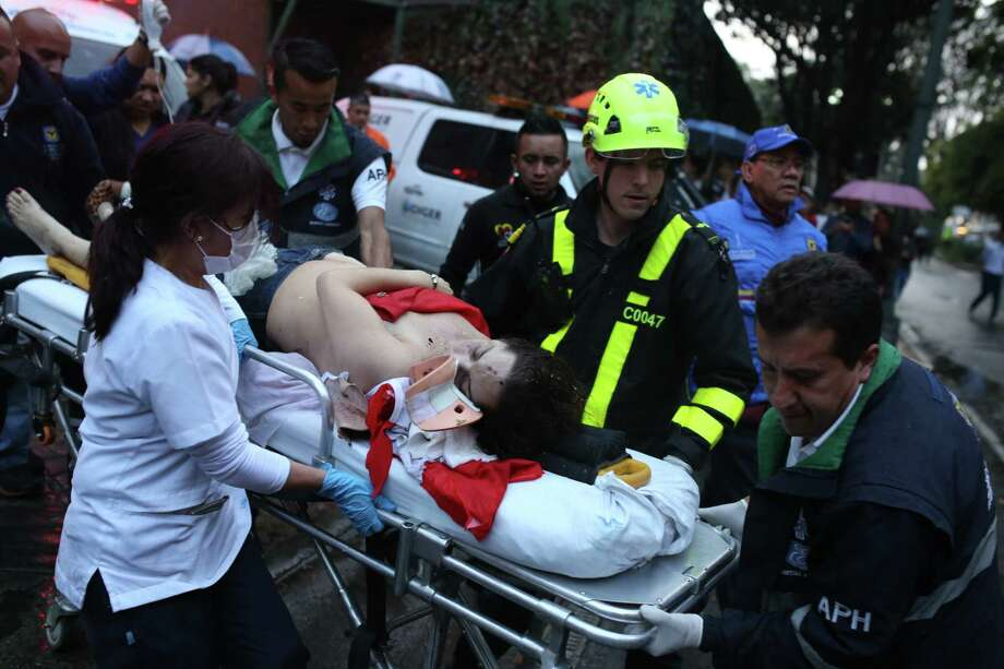 A woman is evacuated on a gurney after an explosion at the Centro Andino shopping center in Bogota, Colombia, Saturday, June 17, 2017. Authorities reported one woman was killed and 11 people injured. Authorities' attention immediately focused on the country's largest still active rebel group, the National Liberation Army, or ELN, which in February claimed responsibility for a bombing near Bogota's bullring that killed one police officer and injured 20 other people. (AP Photo/Ricardo Mazalan) Photo: Ricardo Mazalan, STF / Copyright 2017 The Associated Press. All rights reserved.