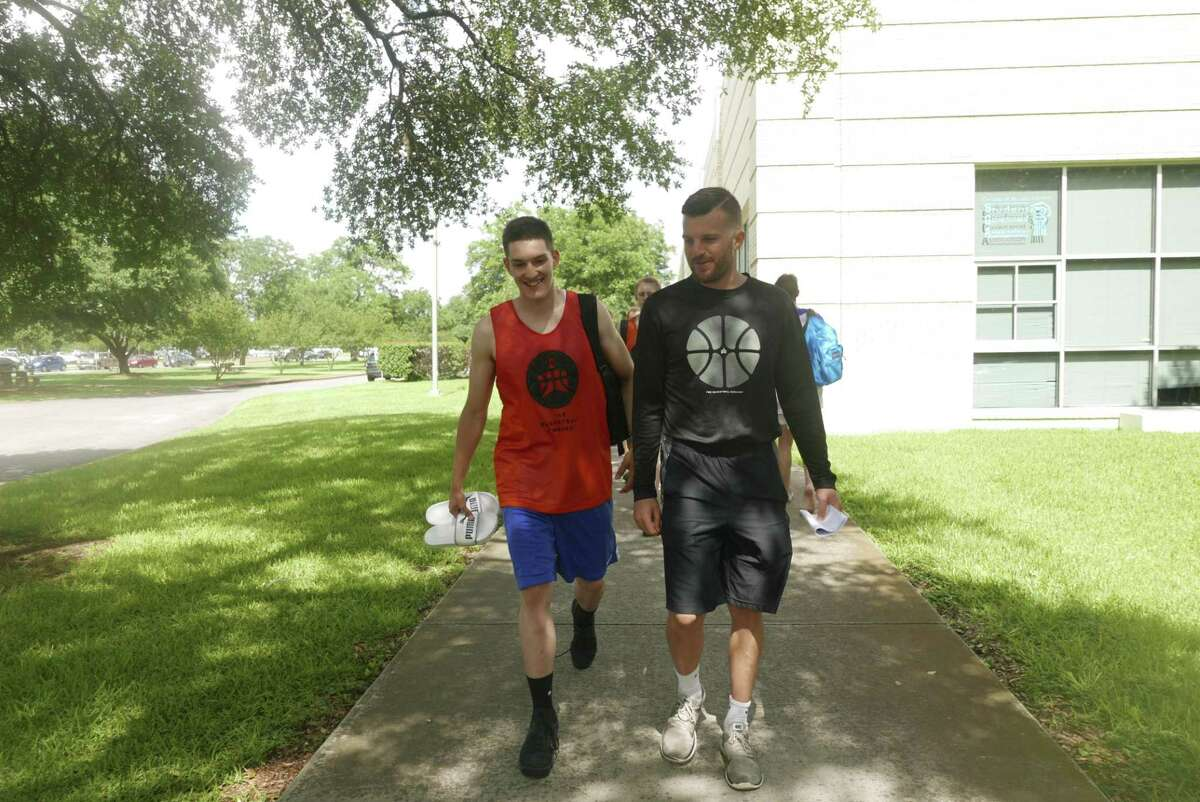 Andi Vrapcani, who hails from Kosovo, left, walks with coach Dustin Karrer on the campus of Our Lady of the Lake University during the Basketball Embassy summer basketball camp on Tuesday, June 13, 2017.