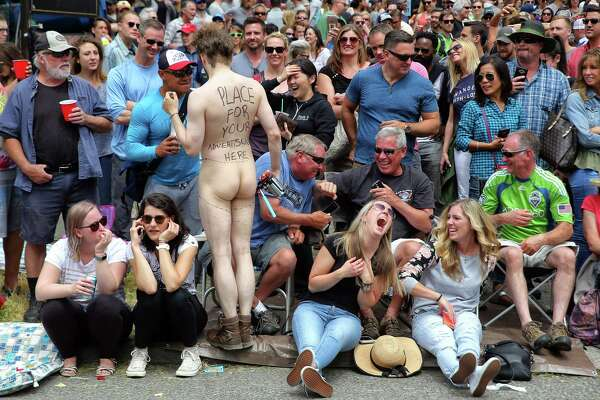 "A man with ""place for your advertisement here"" written on his back lets members of the crowd draw on him during the Fremont Solstice Parade on Saturday, June 17, 2017."