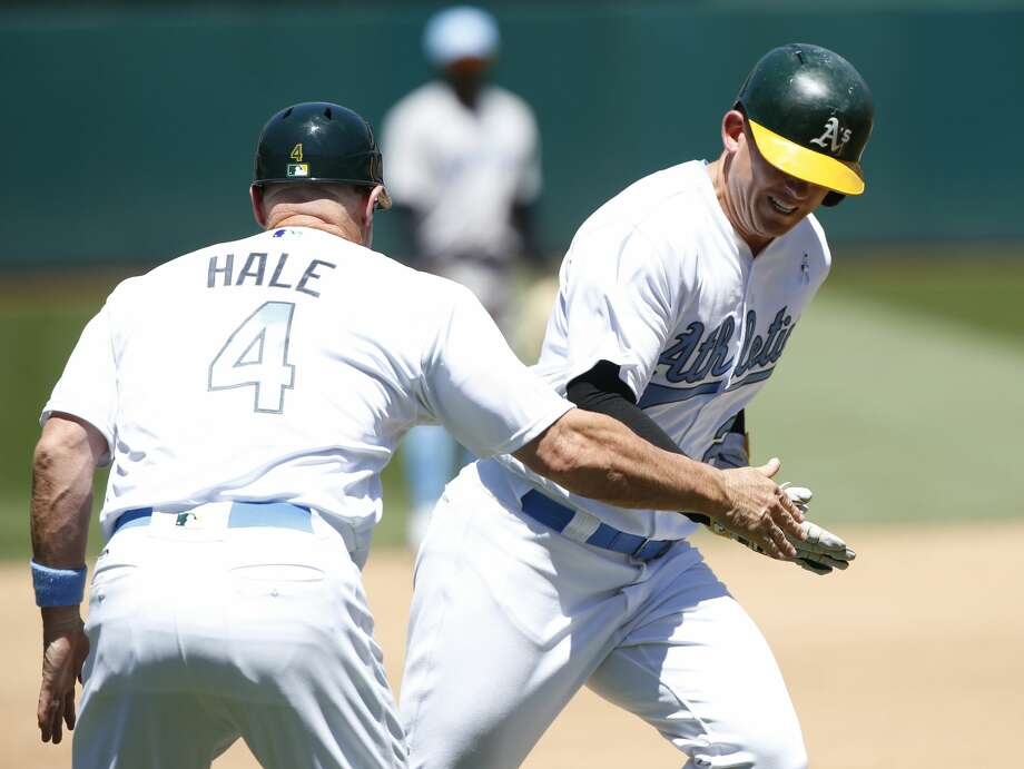 The Oakland Athletics' Ryon Healy is congratulated by third base coach Chip Hale (4) as he rounds the bases on a home run against the New York Yankees in the fourth inning at Oakland Coliseum in Oakland, Calif., on Saturday, June 17, 2017. The A's won, 5-2. (Jim Gensheimer/Bay Area News Group/TNS) Photo: Jim Gensheimer/TNS