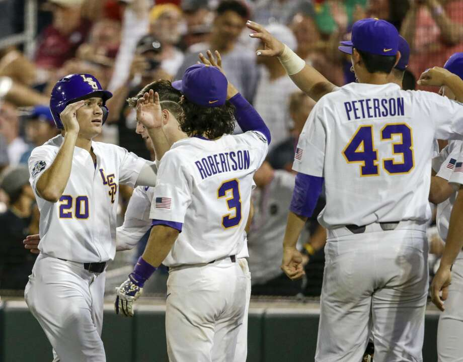 LSU's Antoine Duplantis (20) celebrates with teammates including Kramer Robertson (3) after he scored the go-ahead run against Florida State on a single by Greg Deichmann during the eighth inning of an NCAA College World Series baseball game in Omaha, Neb., Saturday, June 17, 2017. LSU won 5-4. (AP Photo/Nati Harnik) Photo: Nati Harnik/Associated Press