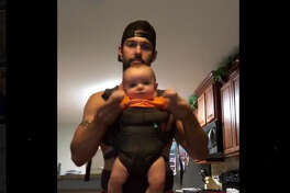 """Robert Douglas and 6-month-old Dantyn spend Saturday night dancing.   """"I think my face shows I'm trying harder than he is."""""""