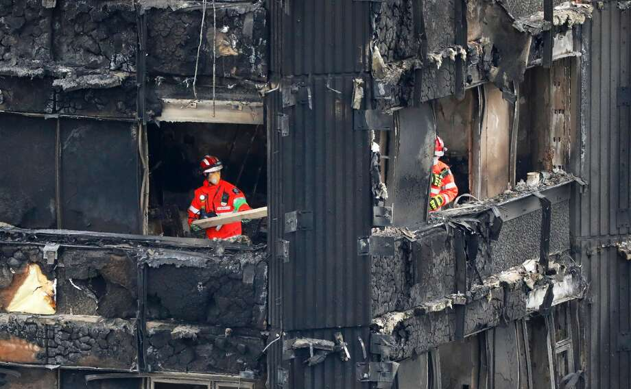 Members of the emergency services work on the middle floors of the charred remnains of the Grenfell Tower block in Kensington, west London, on June 17, 2017, follwing the June 14 fire at the residential building. Angry London residents heckled Prime Minister Theresa May and stormed local authority headquarters Friday as they demanded justice for the victims of the June 14 Kensington tower block fire that left 30 people dead, with dozens more unaccounted for. Photo: TOLGA AKMEN/AFP/Getty Images