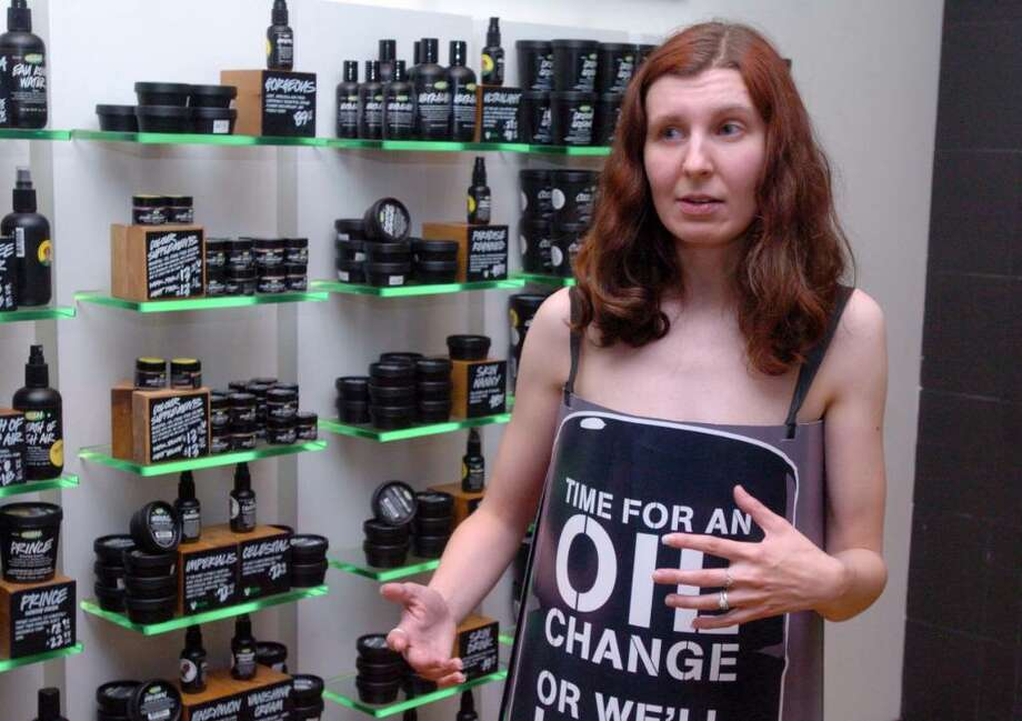 Suzanne Bliven, of Waterbury, an employee of Lush - Fresh Handmade Cosmetics at the Danbury Fair mall, wears only a sign shaped like a barrel to protest the use of Canadian Tar Sands Wednesday, June 9, 2010. Located in Alberta, Canada, mining companies remove forests to access land that is rich in crude oil, which upsets environmentalists and Lush. Photo: Chris Ware / The News-Times