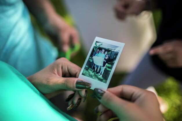 Karen Rodriguez, 18, holds an instant photograph of her family on Father's Day, Sunday, June 18, 2017, in Houston. Photo: Marie D. De Jesus, Houston Chronicle / © 2017 Houston Chronicle