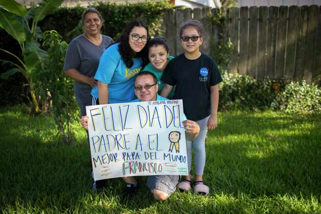 "Juan Rodriguez, holds a sign made by his daughters in Spanish on Father's Day, Sunday, June 18, 2017, in Houston. In English, the sign says ""Happy Father's Day to the best father in the world, Francisco."" Francisco is the middle name of Juan. Left to right is Celia Rodriguez, and their daughters, Rebecca Rodriguez, 15, Karen Rodriguez, 18, and ten-year-old, Kimberly Rodriguez. Photo: Marie D. De Jesus, Houston Chronicle / © 2017 Houston Chronicle"