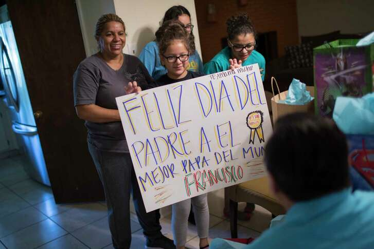 "Kimberly Rodriguez, center, 10, surprises her father Juan Rodriguez with a Father's Day sign written in Spanish  which reads, ""Happy Father's Day to the best father in the world, Francisco."" Francisco is the middle name of Juan. Sunday, June 18, 2017, in Houston."