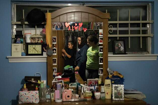 The reflection of Kimberly Rodriguez, 10, Rebecca Rodriguez, 15, and Karen Rodriguez, 18, is visible on the mirror in Karen's room as they prepare to wrap up Father's Day gifts, Friday, June 16, 2017, in Houston. Photo: Marie D. De Jesus, Houston Chronicle / © 2017 Houston Chronicle
