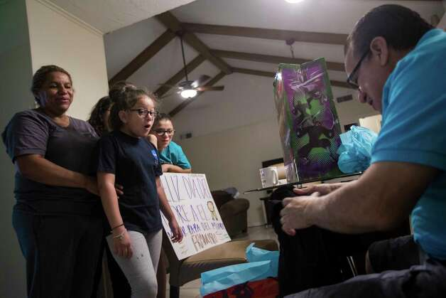 Kimberly Rodriguez, center, 10, reacts as her father Juan Rodriguez, right, opens the gifts Kimberly and her sisters bought for their him as part of Father's Day morning, Sunday, June 18, 2017, in Houston. The sisters tried their best to make this holiday as special as possible for him just in case he gets deported to El Salvador at the end of June. Photo: Marie D. De Jesus, Houston Chronicle / © 2017 Houston Chronicle