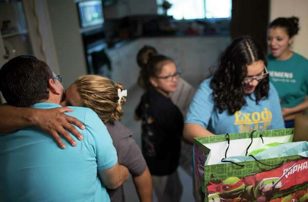 Celia Rodriguez embraces her husband Juan Rodriguez while their daughters Kimberly Rodriguez, center, 10, Rebecca Rodriguez, 15, and Karen Rodriguez, 18, look at the gifts they got for Juan for Father's Day, Sunday, June 18, 2017, in Houston. Photo: Marie D. De Jesus, Houston Chronicle / © 2017 Houston Chronicle