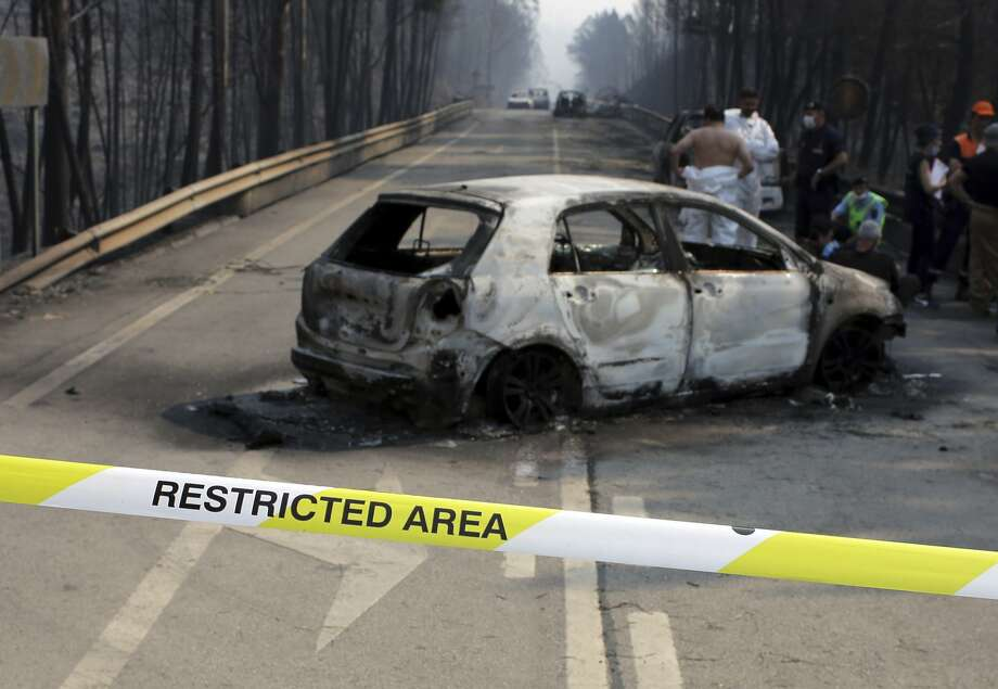 Police investigators stand by a burnt car on the road between Castanheira de Pera and Figueiro dos Vinhos, central Portugal, Sunday, June 18 2017. Raging forest fires in central Portugal killed at least 50 people, many of them trapped in their cars as flames swept over a road Saturday evening. (AP Photo/Armando Franca), Photo: Armando Franca, Associated Press