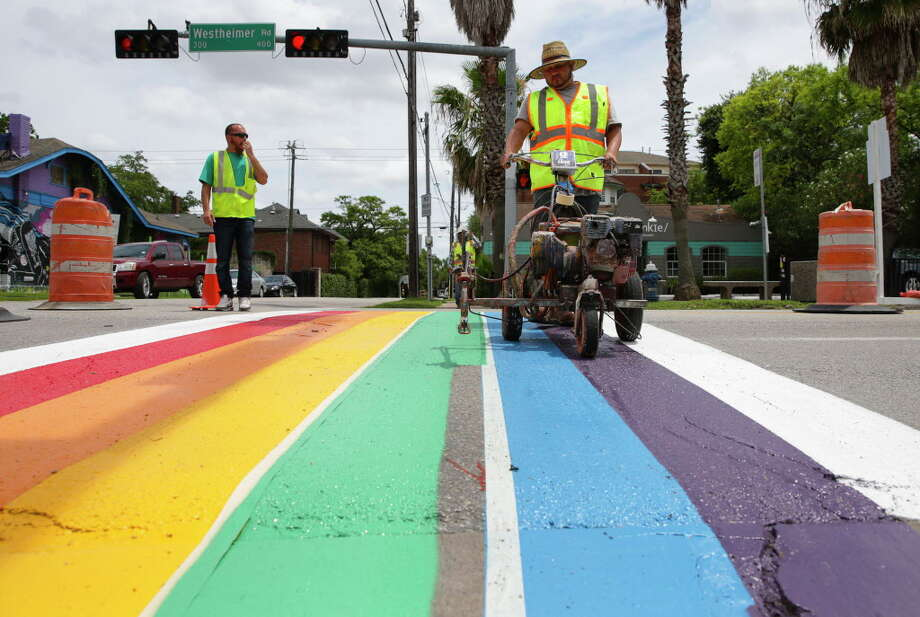 Eduardo Ortiz operates the machine to put down the green clolor to finish painting the Rainbow Flag crosswalk on the northside of the Westheimer Road and Taft Street intersection Saturday, June 17, 2017, in Houston. The Rainbow Flag crosswalks are ment to honor Alex Hill, who died from a hit-and-run accident at this intersection in 2013,  and it would be the state of Texas' first Rainbow Flag crossing. Photo: Yi-Chin Lee, Houston Chronicle / © 2017  Houston Chronicle