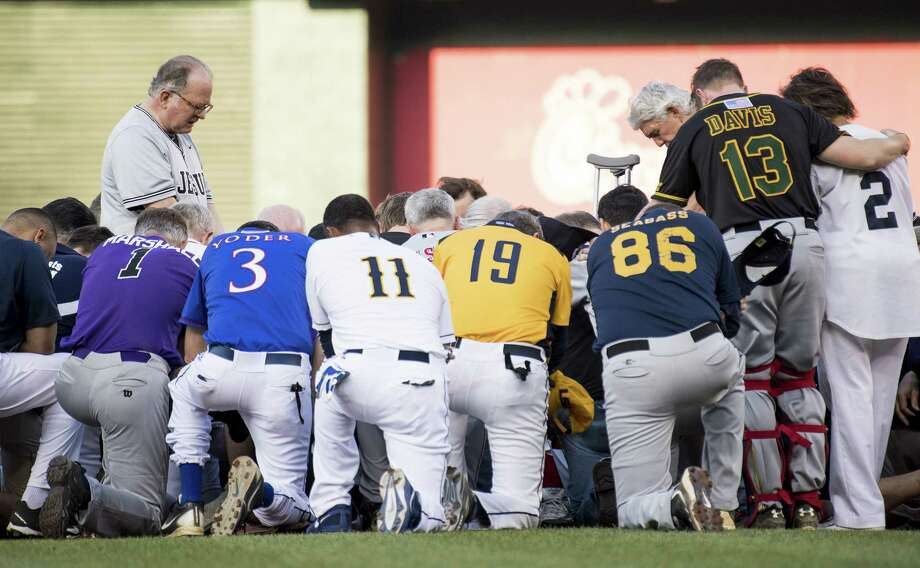 Patrick Conroy, chaplain of the House of Representatives, left, leads a moment of prayer before the start of the Congressional Baseball Game on Thursday in Washington, D.C. Photo: Bill Clark/CQ Roll Call/Newscom, MBR / Zuma Press
