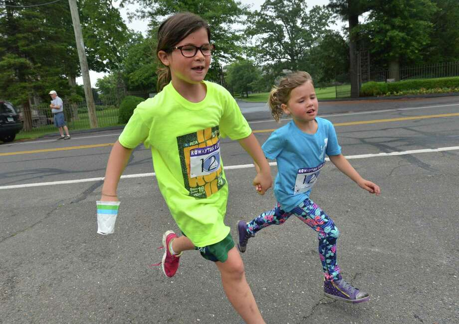 Sisters Campbell and Patton Crawford hold hands as they make the turn to the finish line at the Rowayton Civic Association's 38th annual Rowayton Fun Run on Sunday in Rowayton. Photo: Alex Von Kleydorff / Hearst Connecticut Media / Norwalk Hour