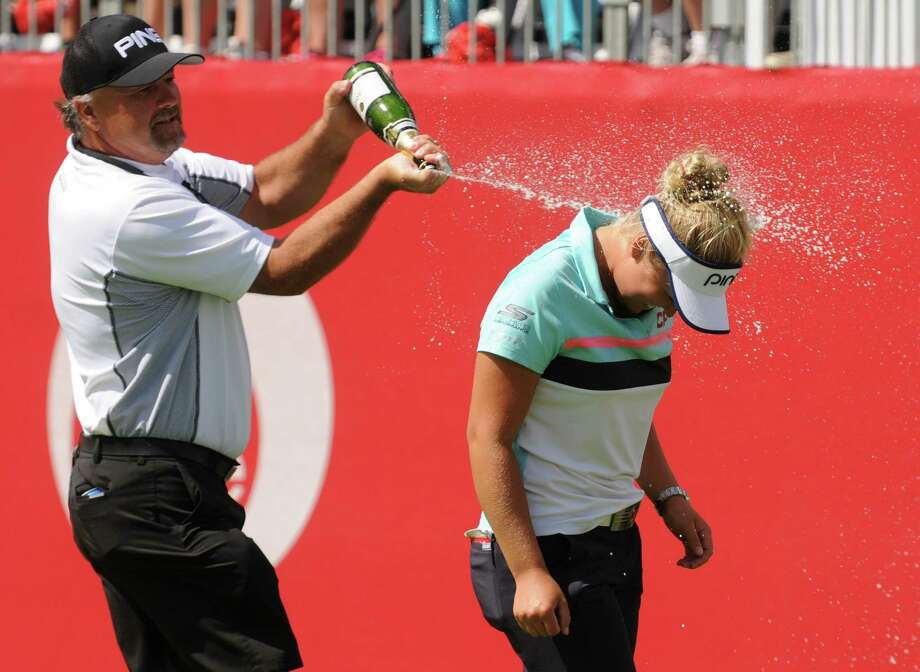 Dave Henderson, left, sprays his daughter Brooke Henderson, of Canada, with champagne after she won  after winning the Meijer LPGA Classic golf tournament at Blythefield Country Club. Sunday, June 18, 2017, in Grand Rapids, Mich.. (Cory Olsen/The Grand Rapids Press via AP) Photo: Cory Olsen, MBO / The Grand Rapids Press