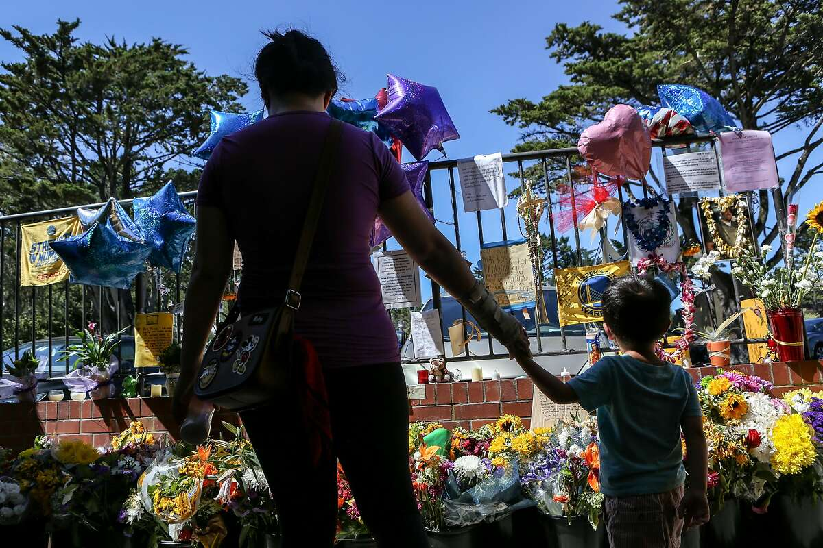 Marie Chen and son Damien Wu, 4, read messages left to Mike Lefti, one of the victims in the UPS shootings last week, at a memorial site in a Diamond Heights shopping center on Sunday, June 18, 2017 in San Francisco, Calif.