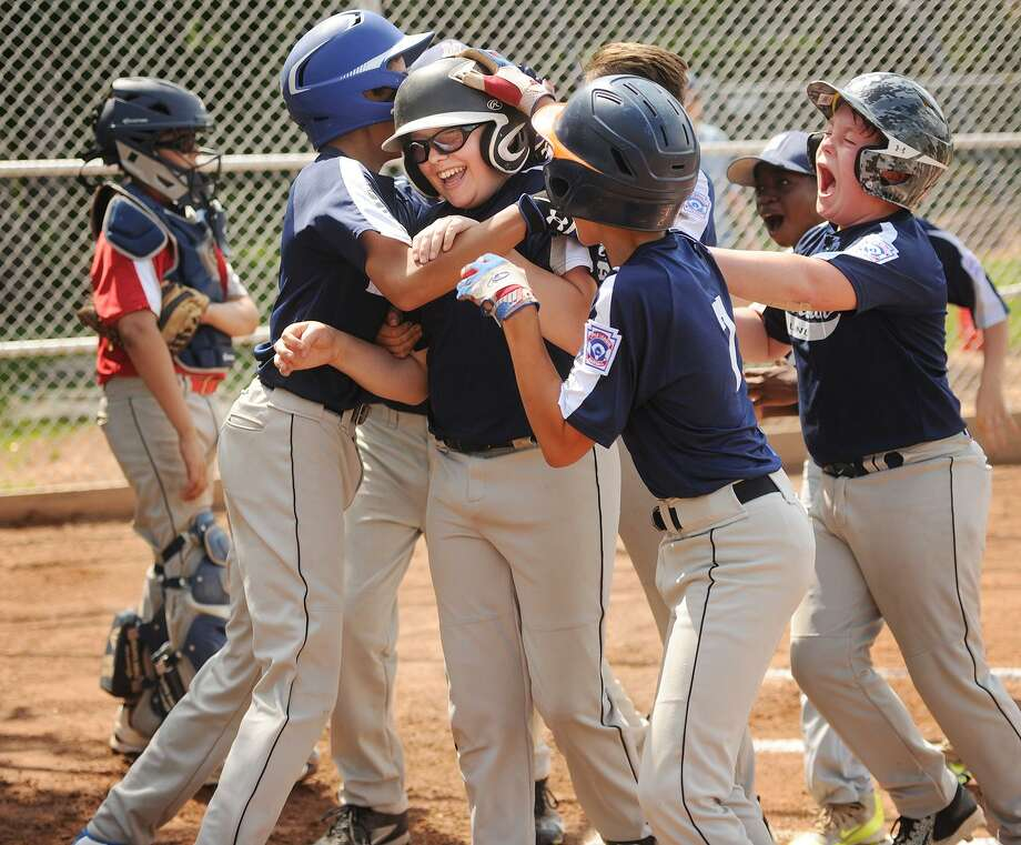 Klaus Schroeder is mobbed by his teammates at home plate after belting a three run home run in the 7th inning to win the first of two games to win the Norwalk Little League championship at Broad River Field in Norwalk, Conn. on Sunday, June 18, 2017. Norwalk Linen won the game 9-3. Photo: Brian A. Pounds / Hearst Connecticut Media / Connecticut Post