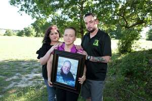 Sandra McCollum, center, holds a portrait of her late husband Larry McCollum with his children.